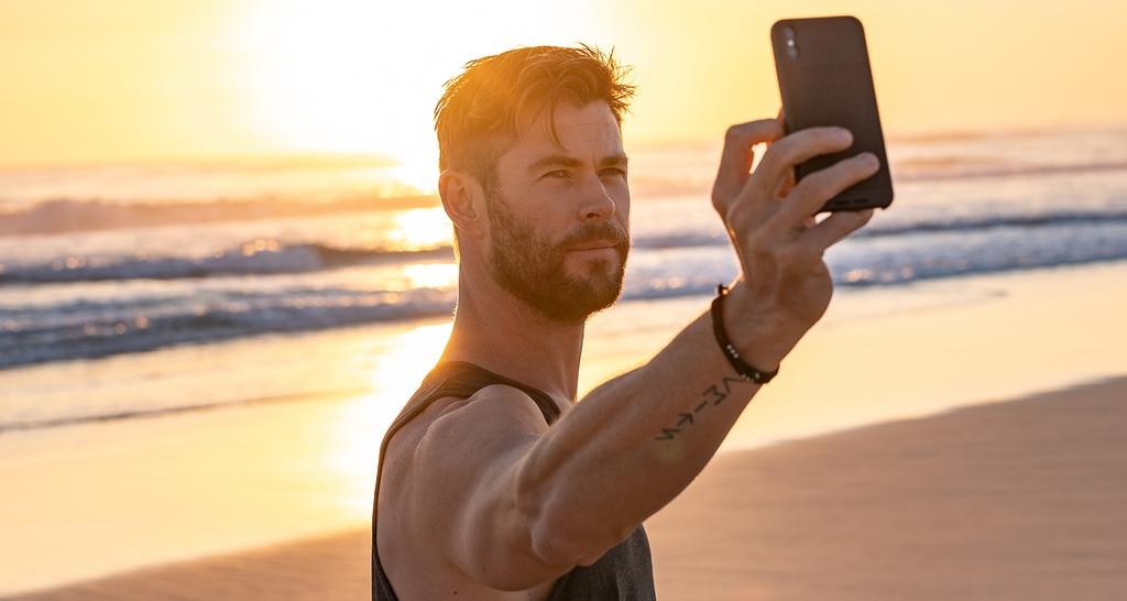 Chris Hemsworth taking a selfie on a sunny beach