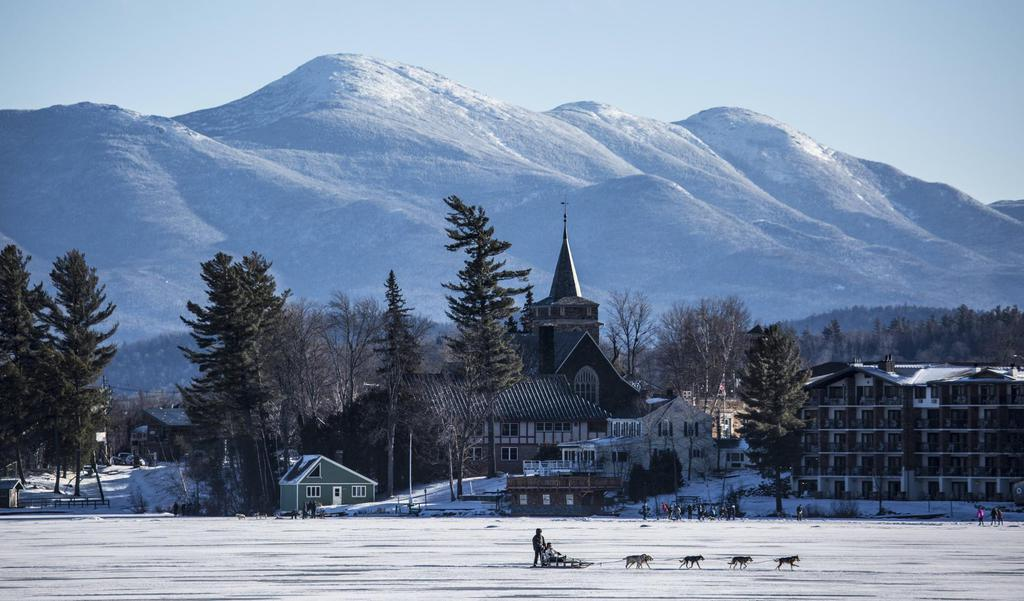 Lake Placid in the Adirondacks, lodging in distance, dogs pulling a sled upfront.