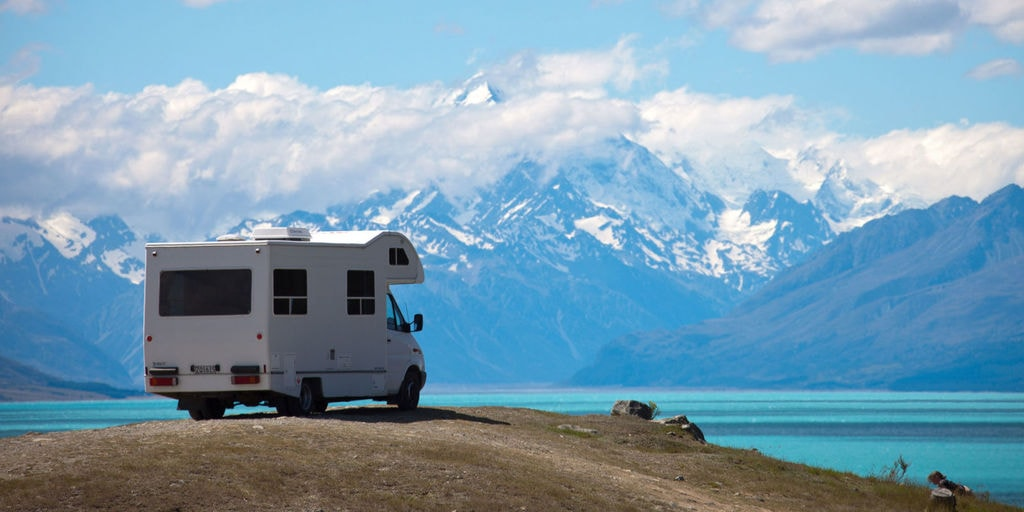 RV parked on a sunny area, lake and mountain view upfront