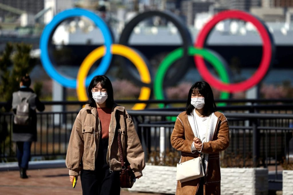 Japanese citizens wearing face masks in front of the Olympic rings in Tokyo